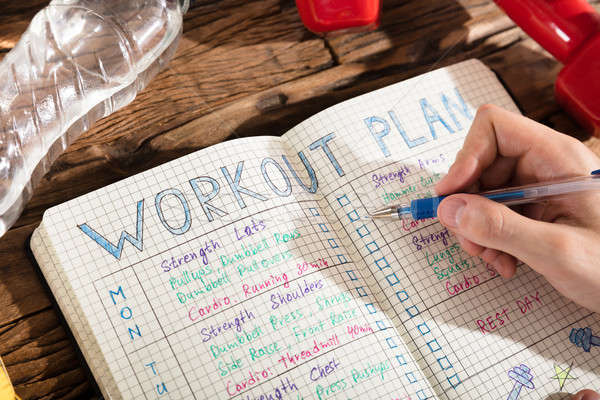 Person Making Note Of Workout Plan On Notebook Stock photo © AndreyPopov