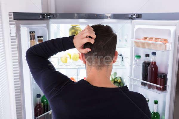 Mylić człowiek patrząc żywności lodówce widok z tyłu Zdjęcia stock © AndreyPopov