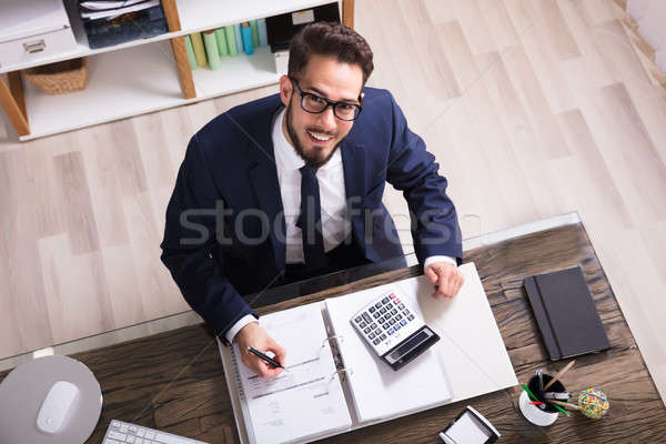 Happy Businessman Calculating Bill In Office Stock photo © AndreyPopov