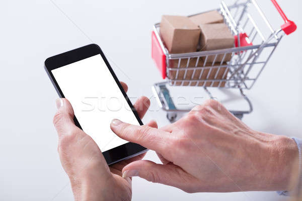 Cart Filled With Boxes And Hand Holding Mobile Phone Stock photo © AndreyPopov