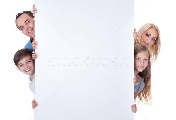 Portrait Of Family Peeping Behind Blank Board Stock photo © AndreyPopov