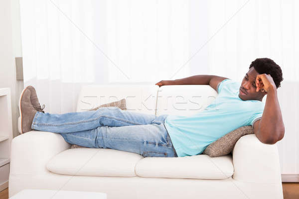 Tembel adam dışarı kanepe endişeli Afrika Stok fotoğraf © AndreyPopov