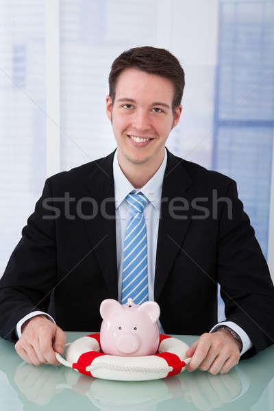 Businessman Protecting Piggybank With Lifebelt Stock photo © AndreyPopov