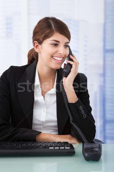 Businesswoman Using Landline Phone In Office Stock photo © AndreyPopov