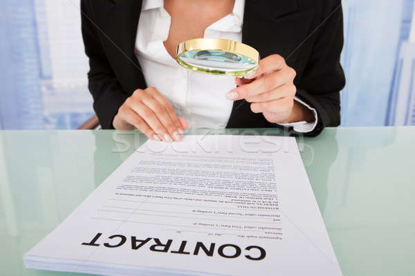 Businesswoman Scrutinizing Contract With Magnifying Glass Stock photo © AndreyPopov