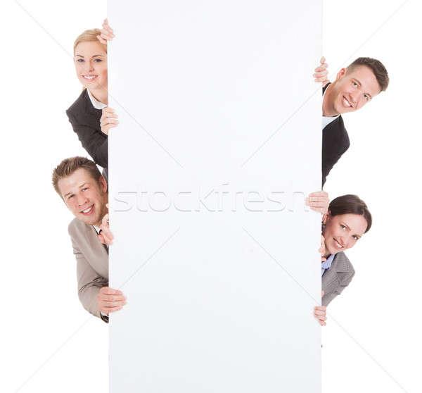 Zdjęcia stock: Ludzi · biznesu · patrząc · za · billboard · portret · uśmiechnięty