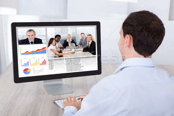 Businessman Video Conferencing With Colleagues On Pc At Desk Stock photo © AndreyPopov