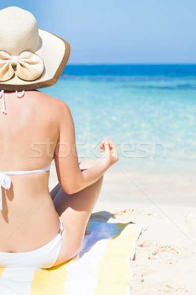 Woman in bikini meditating on beach towel at seashore Stock photo © AndreyPopov