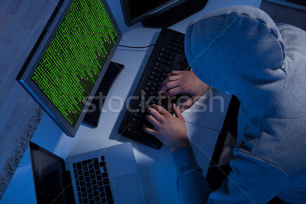 Hacker In Hooded Jacket Using Computer At Table Stock photo © AndreyPopov
