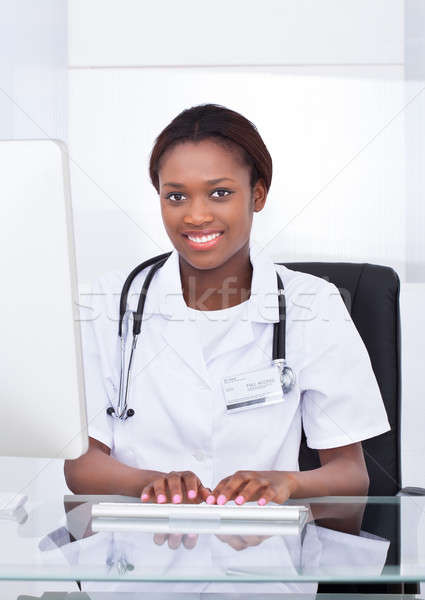 Female Doctor Using Computer At Desk In Hospital Stock photo © AndreyPopov