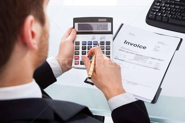 Businessman Calculating Invoice At Office Desk Stock photo © AndreyPopov