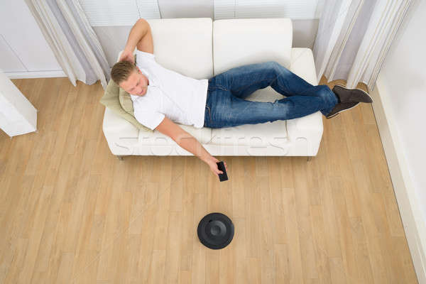 Man Operating Robotic Vacuum Cleaner With Remote Control Stock photo © AndreyPopov