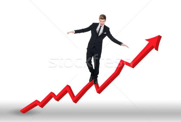 Businessman Balancing On Growing Line Graph Stock photo © AndreyPopov