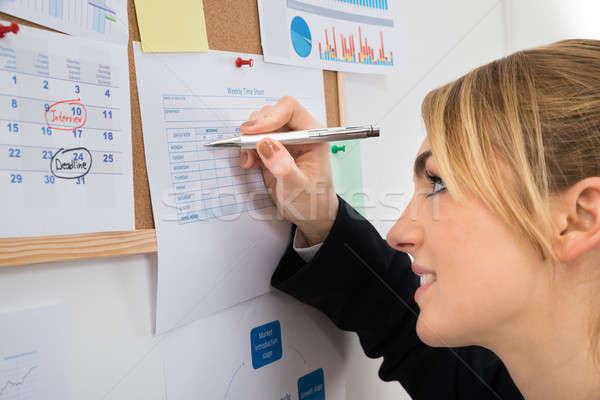 Businesswoman Writing On Weekly Time Sheet Stock photo © AndreyPopov