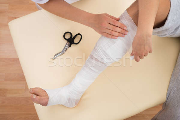 Woman Tying Bandage On Patient's Leg Stock photo © AndreyPopov