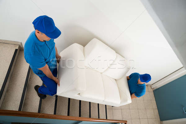 Two Movers Carrying Sofa On Staircase Stock photo © AndreyPopov