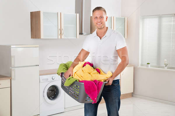 Man Carrying Laundry Basket In Kitchen Room Stock photo © AndreyPopov