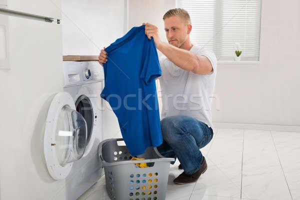 Homem tshirt máquina de lavar roupa moço olhando dispositivo Foto stock © AndreyPopov