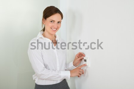 Businesswoman Setting The Temperature On Digital Thermostat Stock photo © AndreyPopov