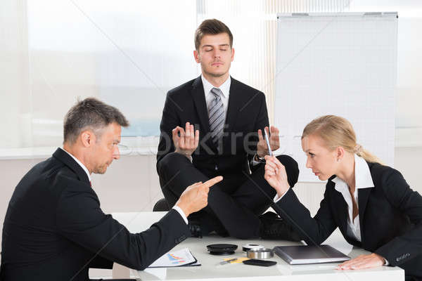 Businesspeople Quarreling In Front Of Businessman Meditating Stock photo © AndreyPopov