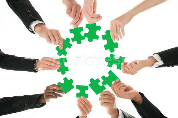 Stock photo: Business Team Joining Jigsaw Pieces In Huddle