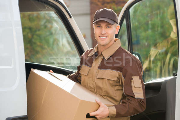 Young Delivery Man Removing Cardboard Box From Truck Stock photo © AndreyPopov