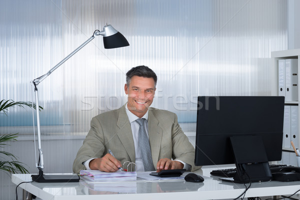 Smiling Accountant Using Calculator While Writing On Documents Stock photo © AndreyPopov