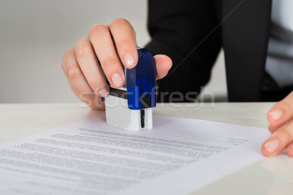 Businesswoman Stamping Contract Document At Desk Stock photo © AndreyPopov