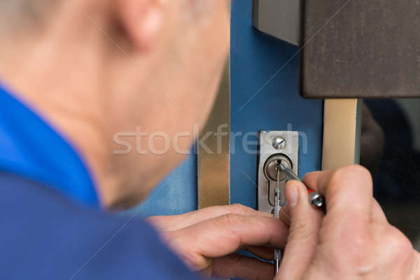 Close-up Of Male Lockpicker Fixing Door Handle At Home Stock photo © AndreyPopov