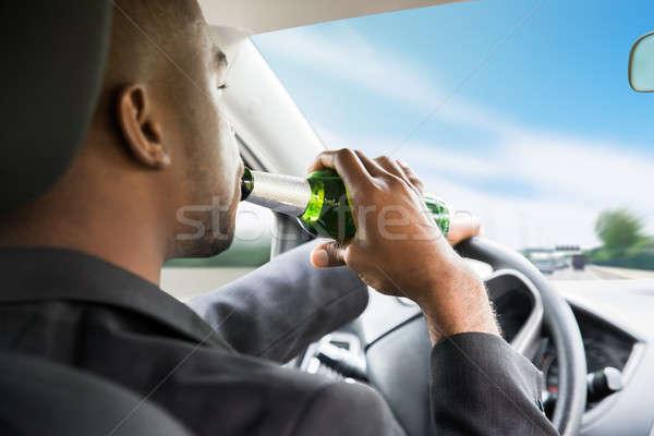 Сток-фото: бизнесмен · питьевой · пива · вождения · автомобилей · вид · сбоку