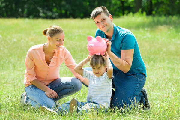 Parents With Their Son Holding Piggy Bank Stock photo © AndreyPopov