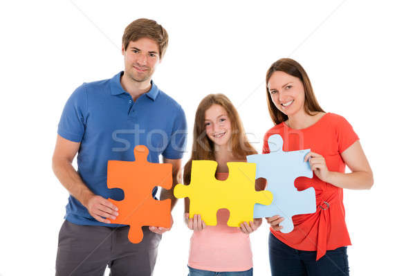 Family Holding Jigsaw Puzzle Pieces Stock photo © AndreyPopov