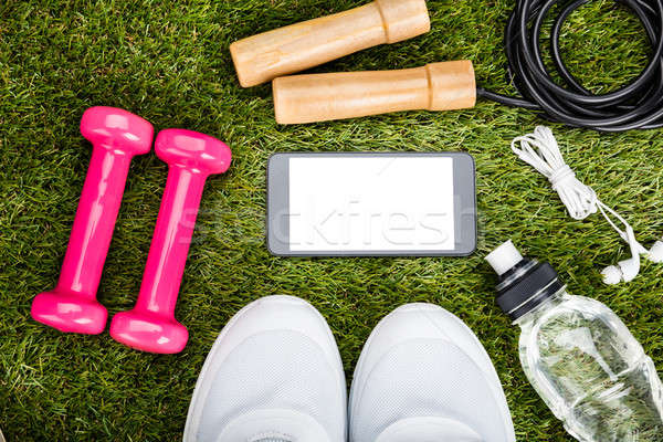 Smartphone With Exercise Equipment On Grassy Field Stock photo © AndreyPopov