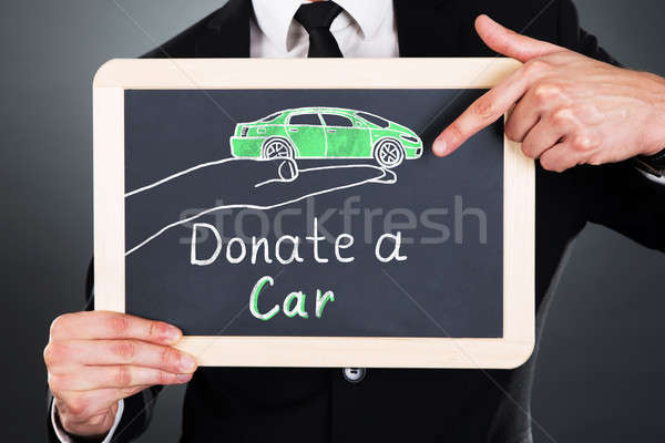 Businessman Showing Car Donation Concept On Slate Stock photo © AndreyPopov
