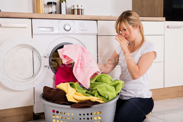 Woman Unloading Smelly Clothes From Washing Machine Stock photo © AndreyPopov