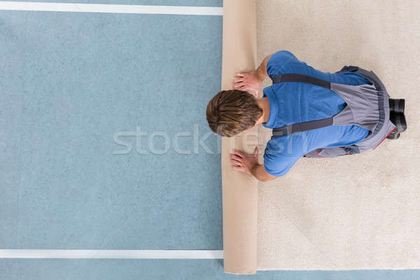 Craftsman In Overalls Unrolling Carpet Stock photo © AndreyPopov