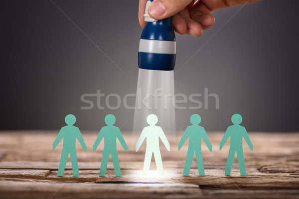 Hand Holding Flashlight Over Paper Man Representing Recruitment Stock photo © AndreyPopov