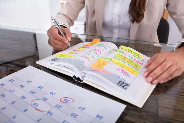 Businesswoman Making Agenda On Diary Stock photo © AndreyPopov