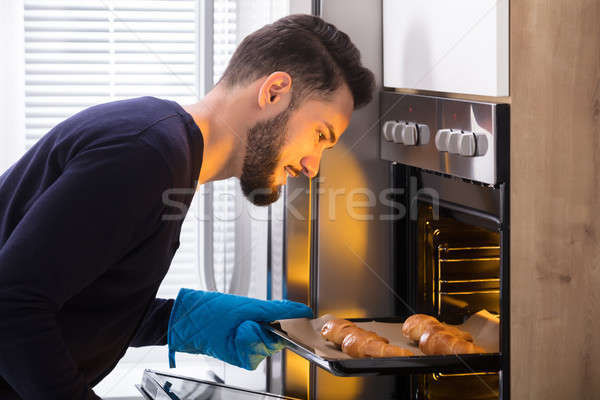 Smiling Young Man Taking Out Tray Of Croissants From Oven Stock photo © AndreyPopov