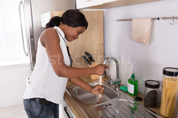 Woman Using Plunger In Blocked Kitchen Sink Stock photo © AndreyPopov