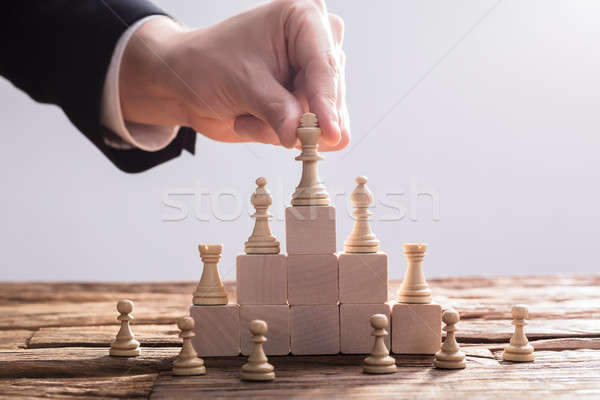 Businessperson Placing King Chess Piece On Top Of Wooden Blocks Stock photo © AndreyPopov