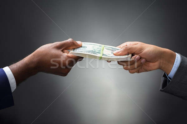 Person Giving Bundle Of Banknote Stock photo © AndreyPopov