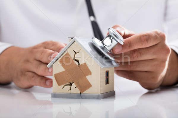 Doctor examining broken house with stethoscope Stock photo © AndreyPopov