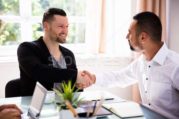 Due imprenditori stringe la mano felice giovani ufficio Foto d'archivio © AndreyPopov