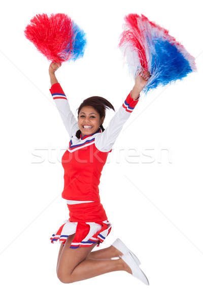 Smiling beautiful cheerleader with pompoms Stock photo © AndreyPopov
