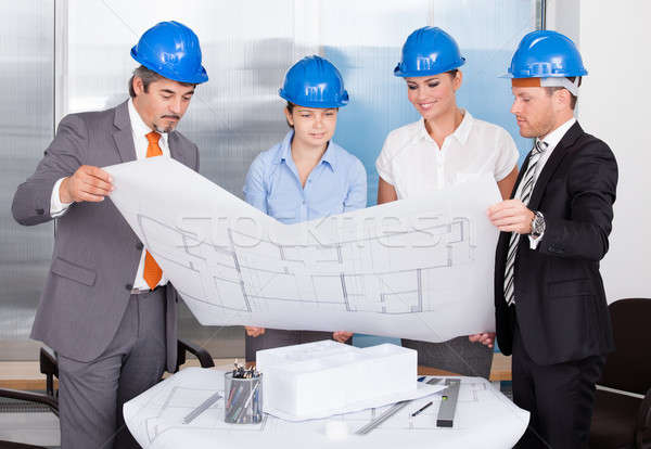 Architects Wearing Blue Hardhat Looking At Blueprint Stock photo © AndreyPopov