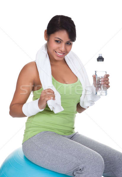 Woman Sitting On Pilates Ball Holding Water Bottle Stock photo © AndreyPopov
