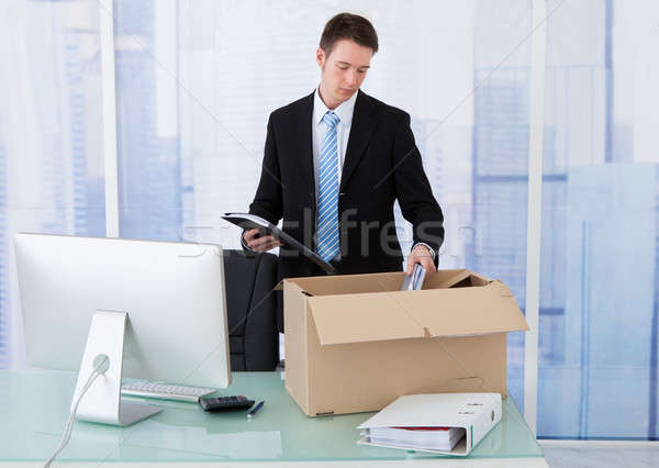 Businessman Collecting Office Supply In Cardboard Box At Desk Stock photo © AndreyPopov