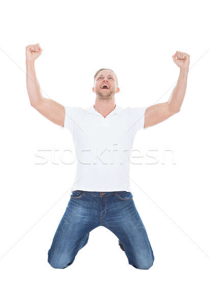 Excited man cheering in jubilation dropping down on his knees Stock photo © AndreyPopov