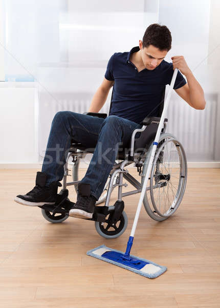 Handicapped Man Mopping Floor While Sitting On Wheelchair Stock photo © AndreyPopov